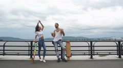 Beautiful guy with the girl on long boards talking to on the waterfront Stock Footage