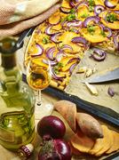 Freshly baked and sliced tarte flambèe with sweet potatoes, red onions, Calvados Stock Photos