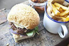 A homemade cheeseburger with watercress and chips Stock Photos