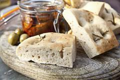 Focaccia with rosemary, dried tomatoes and olives Stock Photos