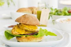 A chicken burger with mango sauce and red onions Stock Photos