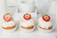 Three strawberry cupcakes topped with buttercream Stock Photos