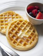 Waffles with butter, maple syrup and berries Stock Photos