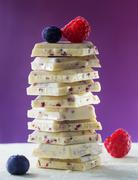 Stack of white chocolate with the raspberries and blueberries Stock Photos