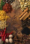 Assorted spices on wooden board Stock Photos