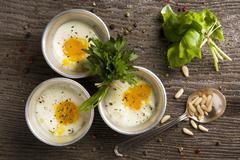 Poached eggs in metal dishes Stock Photos