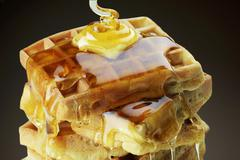 A stack of waffles with butter and dripping honey Stock Photos