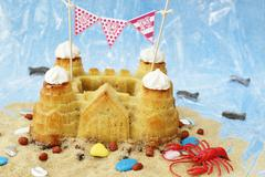 A sandcastle cake with beach decorations Stock Photos