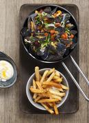 Mussels in a vegetable and herb broth served with fries and aioli Stock Photos