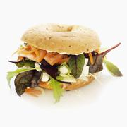 A bagel with feta cheese, lettuce, tomato and carrot Stock Photos