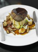 A beef medallion on a bed of mashed potatoes and parsnips with gravy and Stock Photos