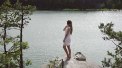 Young beautiful teenager girl standing on stone near mountain lake Stock Footage