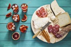An Italian appetiser platter next to glasses of aperitifs garnished with slices Stock Photos
