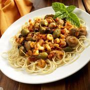 Spaghetti with tiny shrimps, olives, capers, garlic and mushrooms (Sicily) Stock Photos