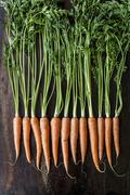 A row of carrots on a wooden surface Stock Photos