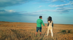 Young Man and woman holding hands and walking through a wheat field, sunset Stock Footage
