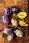 Fresh plums on a wooden board (seen from above) Stock Photos