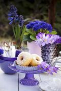 Doughnuts on a table outside decorated with crockery and blue and purple and Stock Photos