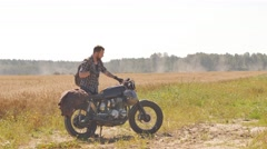 A man on the vintage custom cafe racer riding in a field Stock Footage