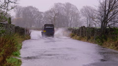 CAR DRIVES THROUGH FLOOD APPERSETT HAWES Stock Footage