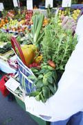 Fresh vegetables and herbs in a checked shopping bag Stock Photos