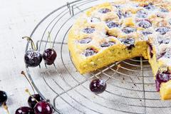 Cherry cake with icing sugar on a wire rack Stock Photos