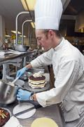 A chef decorating a layer cake with frosting Stock Photos