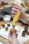 A chef filling a profitable with cream Stock Photos
