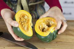 A woman holding two halves of acorn squash Stock Photos