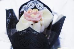 An elegant praline decorated with a rose in a black paper case Stock Photos
