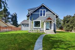 Blue clapboard siding house with grass filled front yard. Northwest, USA Stock Photos
