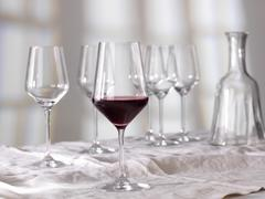 A half full glass of red wine in front of empty glasses and a caraffe Stock Photos