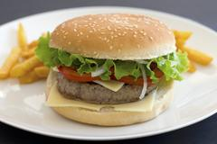 A cheeseburger with tomatoes and lettuce Stock Photos