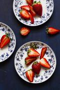 Fresh strawberries, whole and halved, on floral-patterned plates Stock Photos