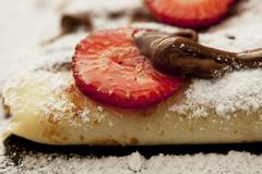 Crepes with chocolate sauce and strawberries (close up) Stock Photos