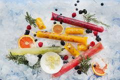 Ice lollies with berries and fruits on ice cubes Stock Photos