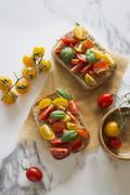Open sandwich with colourful tomatoes and basil Stock Photos