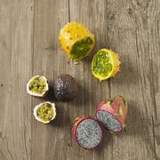 Various exotic fruits on a wooden surface over (passion fruit, red pitahaya, Stock Photos