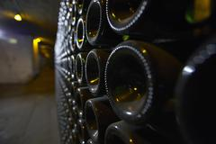 A close-up of bottle bottoms in an aisle of a wine cellar Stock Photos
