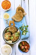 Falafel with hummus, tomato salad, unleavened bread and grated carrots Stock Photos