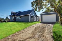 Backyard view of  blue siding house. Detached garage with ground driveway and Stock Photos