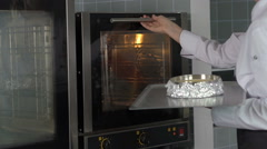 Chef woman doing baking and placing a cake in the oven Stock Footage