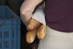 A woman holding three baguettes under her arm Stock Photos