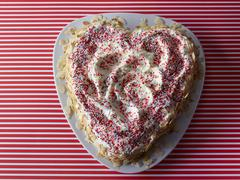 A heart-shaped cake decorated with colourful sprinkles and flaked almonds Stock Photos