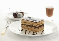 A slice of Opera Cake with cherries and a glass of chocolate liqueur in the Stock Photos