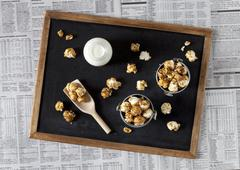 Small buckets of caramel popcorn and milk on a blackboard Stock Photos