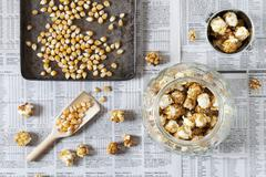 A jar of caramel popcorn next to kernels on a baking tray Stock Photos