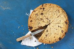 A chocolate chip cookie cake in the tin with a piece missing Stock Photos