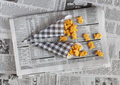 Fish shaped crackers in paper cones on a piece of newspaper Stock Photos