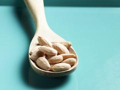 Shelled almonds on wooden spoon Stock Photos